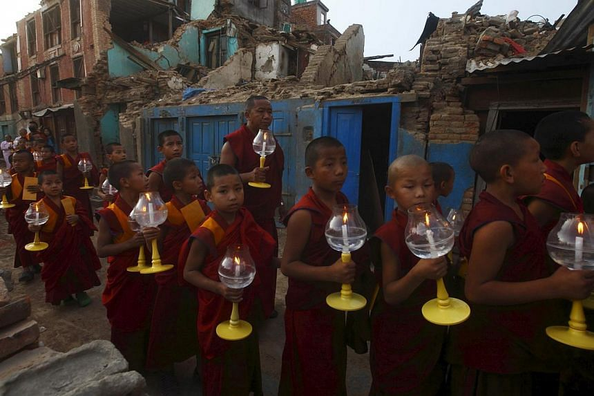 Buddhist monks hold candles as they walk past collapsed buildings during a candlelight vigil as they pray for the earthquakes to cease, in Kathmandu, Nepal, on May 20, 2015. -- PHOTO: AFP
