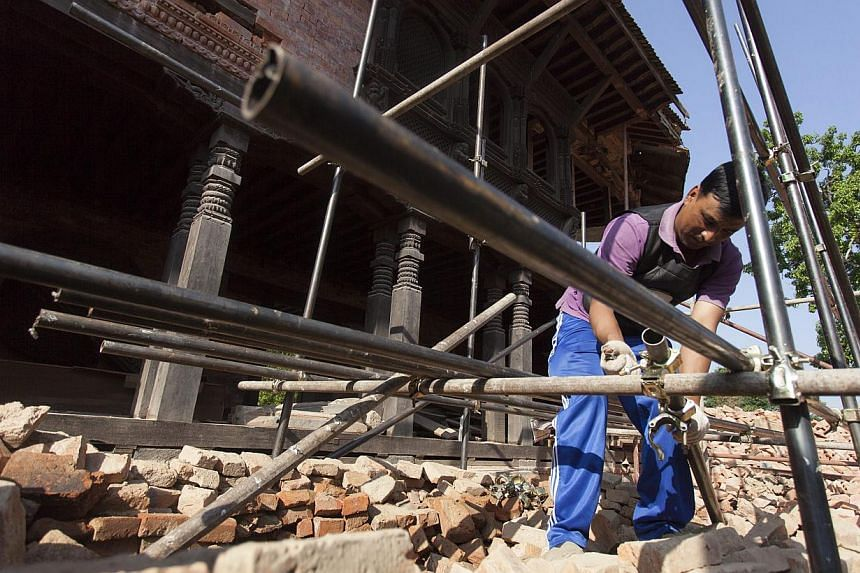 A worker prepares to set iron pipes and beams for the Changunarayan Temple at the Unesco Heritage site on the outskirts of Bhaktapur, Nepal on May 22, 2015. -- PHOTO: EPA