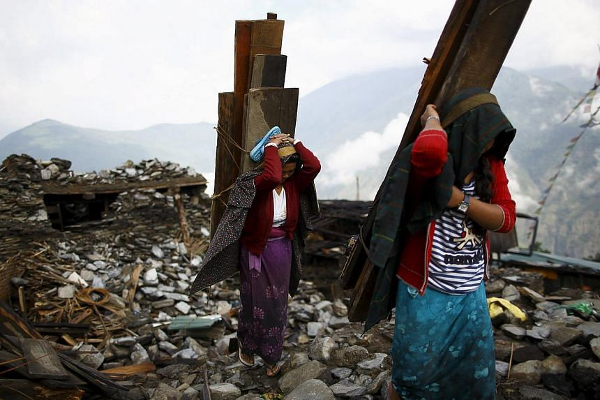 Earthquake victims carry wood recovered from a collapsed house at Barpak village at the epicenter of the April 25 earthquake in Gorkha district, Nepal, on May 21, 2015. -- PHOTO: REUTERS