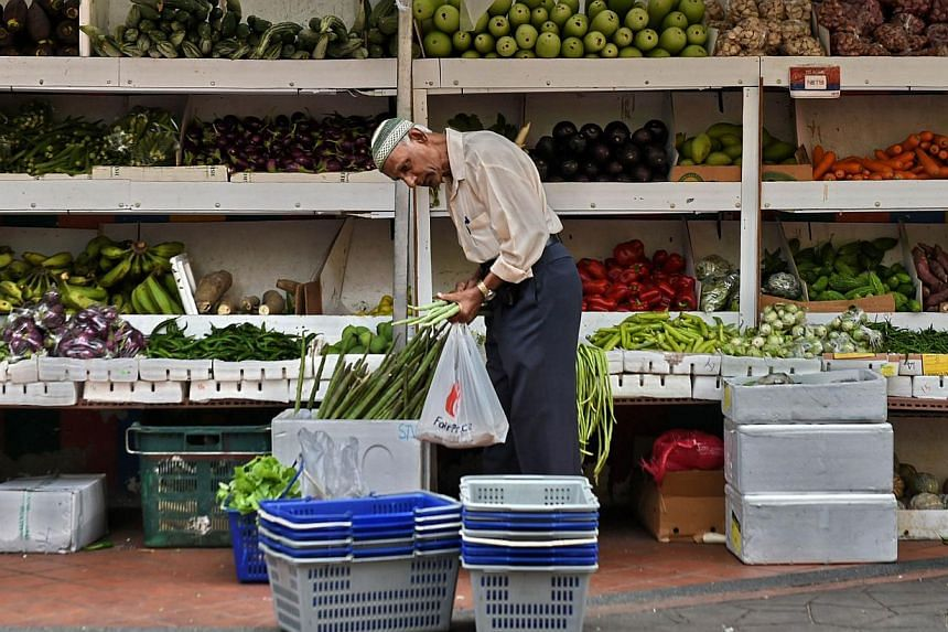 A man shops for vegetables at a market in Singapore on May 8, 2015. -- PHOTO: AFP
