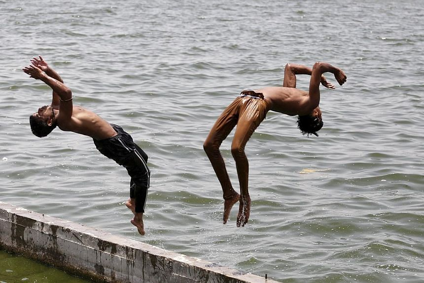 Boys jumping into the Sabarmati river in Ahmedabad yesterday to cool off. Temperatures in the city yesterday reached 43 deg C, according to the India Meteorological Department website. -- PHOTO: EUROPEAN PRESSPHOTO AGENCY