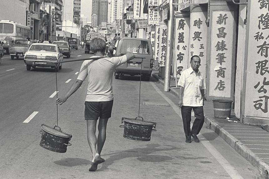 A night-soil worker carrying buckets of night soil to a waiting truck in North Bridge Road during Singapore's earlier years. Back then, diarrhoea was widespread and outbreaks of typhoid fever were common.