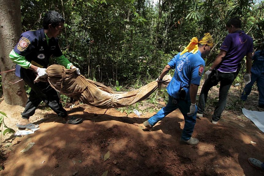 Rescue workers carry a body bag with remains retrieved from a mass grave at a rubber plantation near a mountain in Thailand's southern Songkhla province on May 6, 2015. Malaysian Prime Minister Najib Razak said on Monday that Malaysia will find those