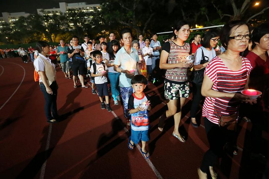 More than 10,000 Buddhist devotees gathered at Hougang Stadium on May 24, 2015, as they held lotus-shaped candles and prayed for peace in the lead up to Vesak day on June 1. National Development Minister Khaw Boon Wan, who is Buddhist, joined the pro