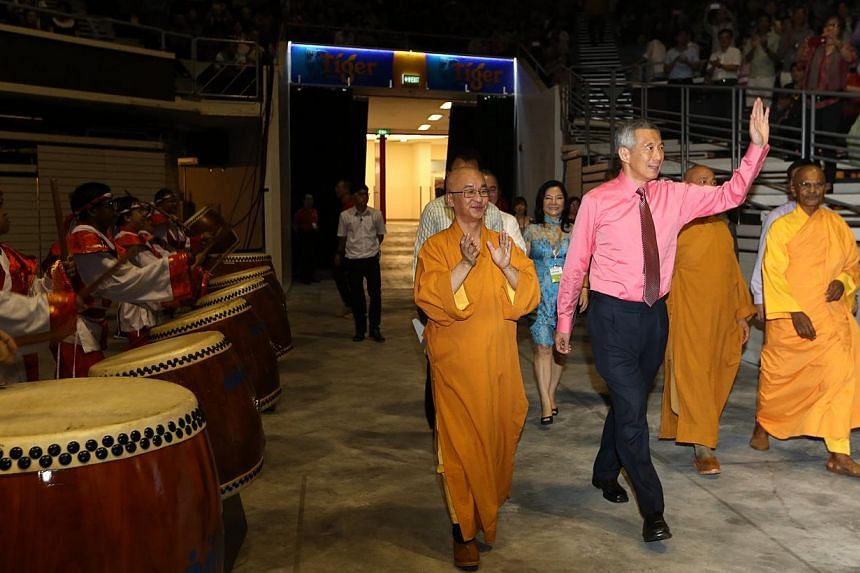 Prime Minister Lee Hsien Loong acknowledging the crowd as he enters the Singapore Indoor Stadium with Venerable Seck Kwang Phing (left), president of the Singapore Buddhist Federation (SBF), for a Vesak Day and SG50 concert organised by the Singapore