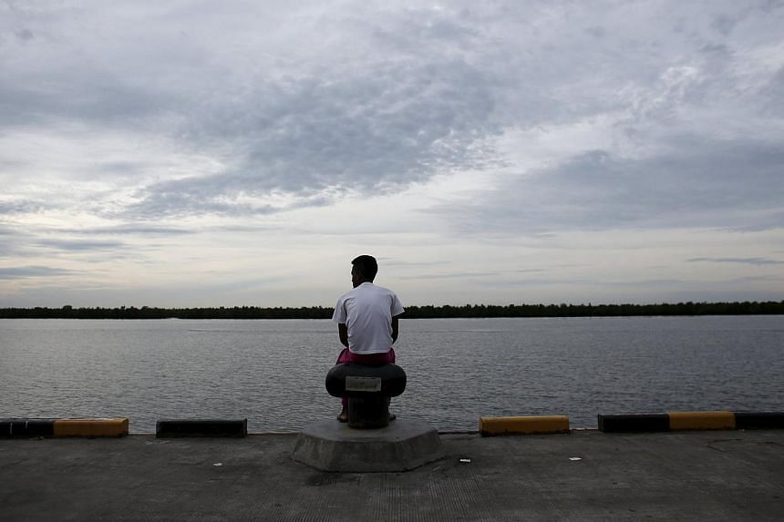 A Bangladeshi migrant who arrived recently by boat sits on a dock near a temporary shelter in Kuala Langsa, in Indonesia's Aceh Province May 25, 2015. Thailand has deployed a helicopter carrier in its waters to serve as a temporary medical and proces