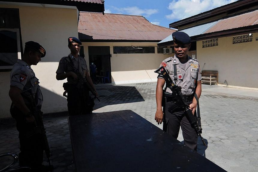 Indonesian police officers stand guard outside a mortuary where the two bodies of suspected islamic militants are stored at a police hospital in Palu, Central Sulawesi, Indonesia, on May 25, 2015. -- PHOTO: EPA