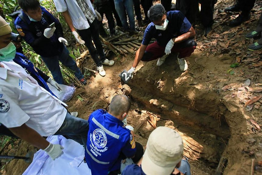 Rescue workers retrieve human remains from graves near the hillside site where shallow graves containing 26 bodies were found on May 1, close to the town of Padang Besar in the southern Thai province of Songkhla on May 13, 2015. -- PHOTO: AFP