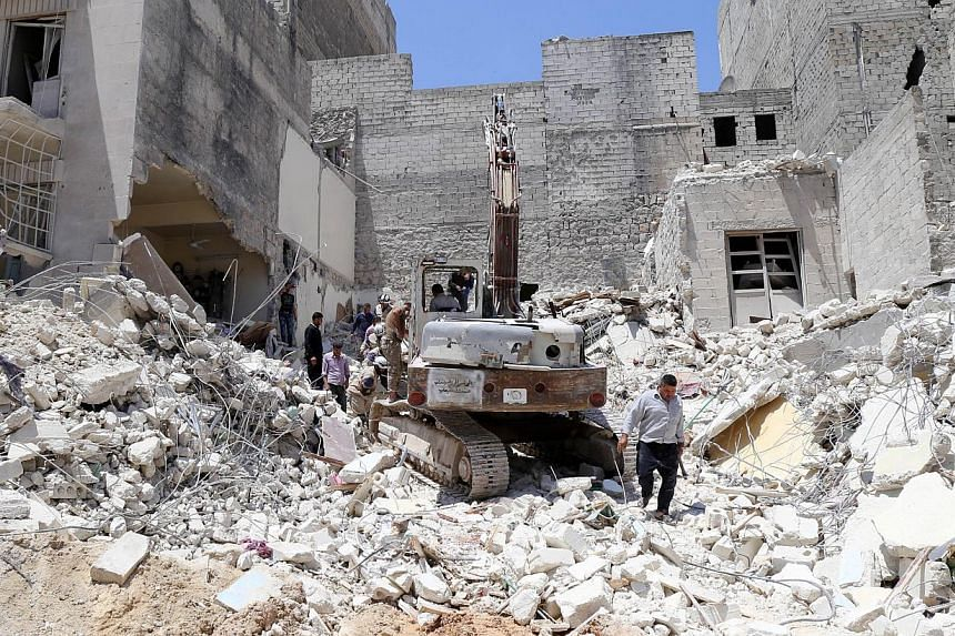 People inspect the rubble of collapsed buildings following a reported airstrike by government forces on May 24, 2015, in the rebel-held al-Sukari neighborhood of the northern city of Aleppo. Home Minister Datuk Seri Dr Ahmad Zahid Hamidi reassured Ma