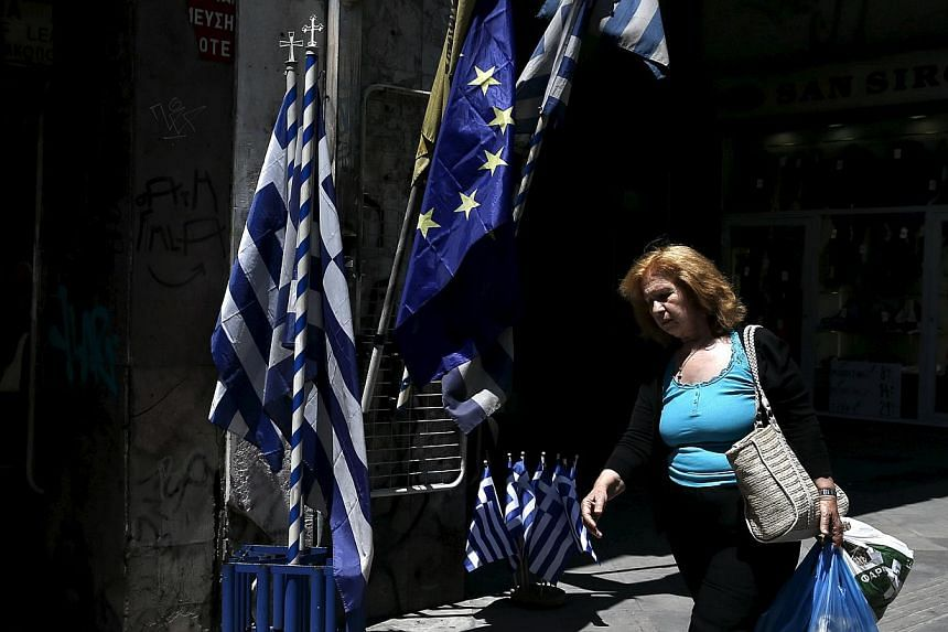 A woman carrying bags of goods makes her way past Greek national flags and European Union flags on display in Athens on May 25, 2015.Struggling Greece will keep on repaying its European Union-International Monetary Fund (IMF) creditors for as l