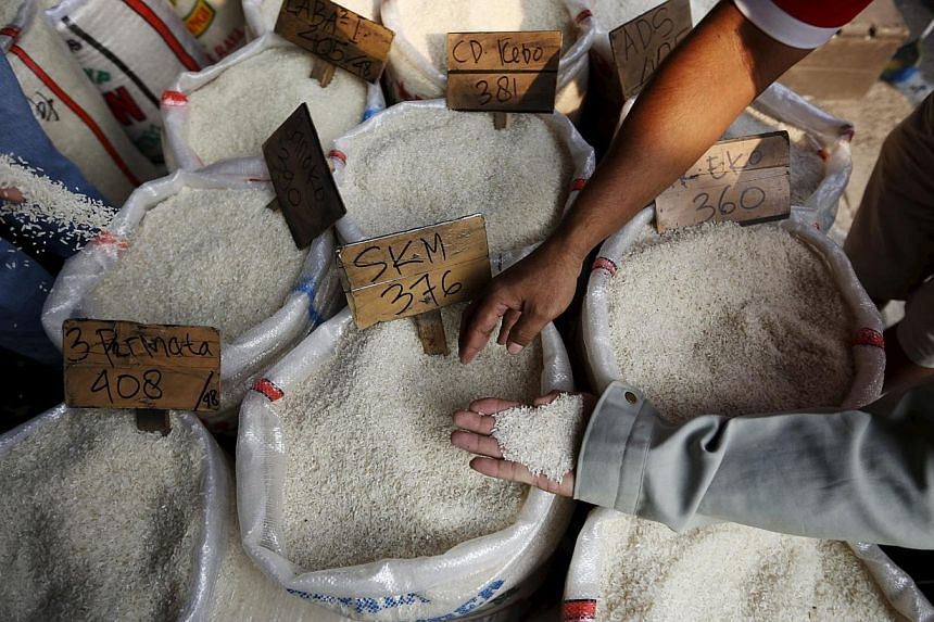 Customers check the quality of rice before buying at a wholesale rice market in East Jakarta, Indonesia, on May 20, 2015.Indonesia's home minister Tjahjo Kumolocalled for a police investigation into the suspected contamination of rice wit