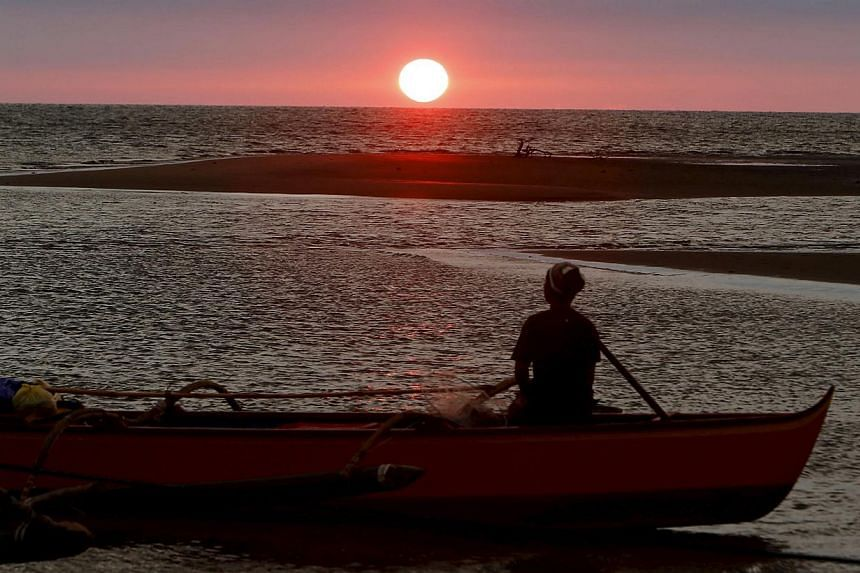 A fisherman watches the sunset in the South China Sea, about 130 nautical miles from Scarborough Shoal in the coastal town of Masinloc, Zambales in northern Philippines on April 21, 2015. -- PHOTO: REUTERS