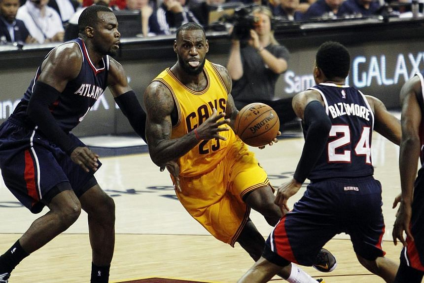 LeBron James (centre) of the Cleveland Cavaliers drives to the basket against (from left) Paul Millsap, Kent Bazemore, and DeMarre Carroll of the Atlanta Hawks during the second half of their NBA Eastern Conference Finals game 3 at Quicken Loans Aren