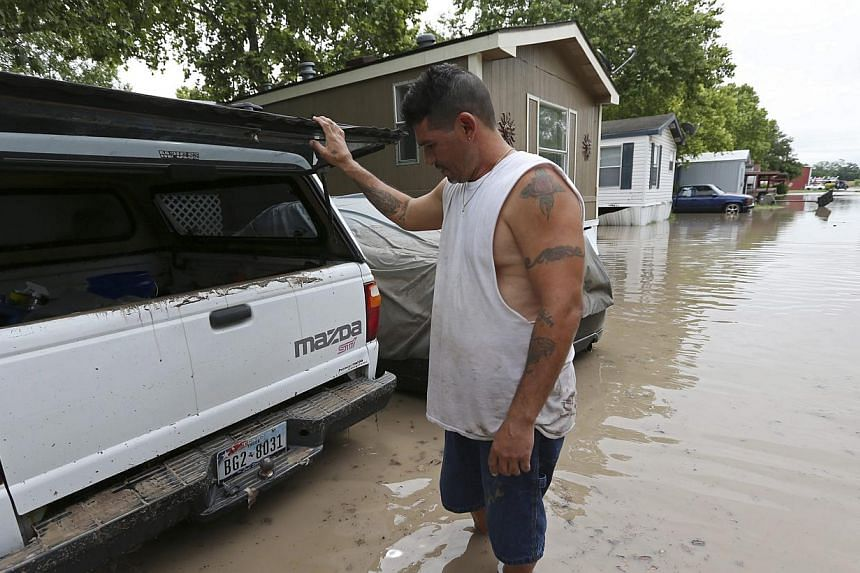 San Marcos resident Keith Varela checks out the damage done to his wife's truck in the San Marcos Mobile Home Park in San Marcos, Texas, on May 24, 2015.Rescuers searched on Monday, May 25, for at least 12 people missing in spectacular flash fl