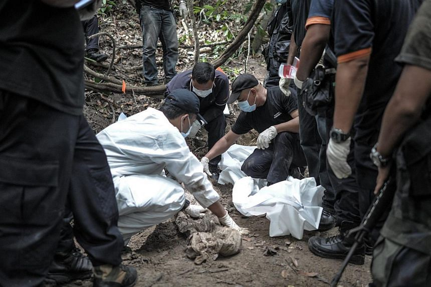 A Royal Malaysian Police forensic team handles exhumed human remains in a jungle at Bukit Wang Burma in the Malaysian northern state of Perlis, which borders Thailand, on May 26, 2015. -- PHOTO: AFP