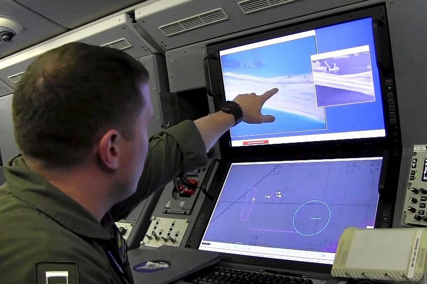 A U.S. Navy crewman aboard a P-8A Poseidon surveillance aircraft views a computer screen purportedly showing Chinese construction on the reclaimed land of Fiery Cross Reef in the disputed Spratly Islands in the South China Sea, in this file still ima