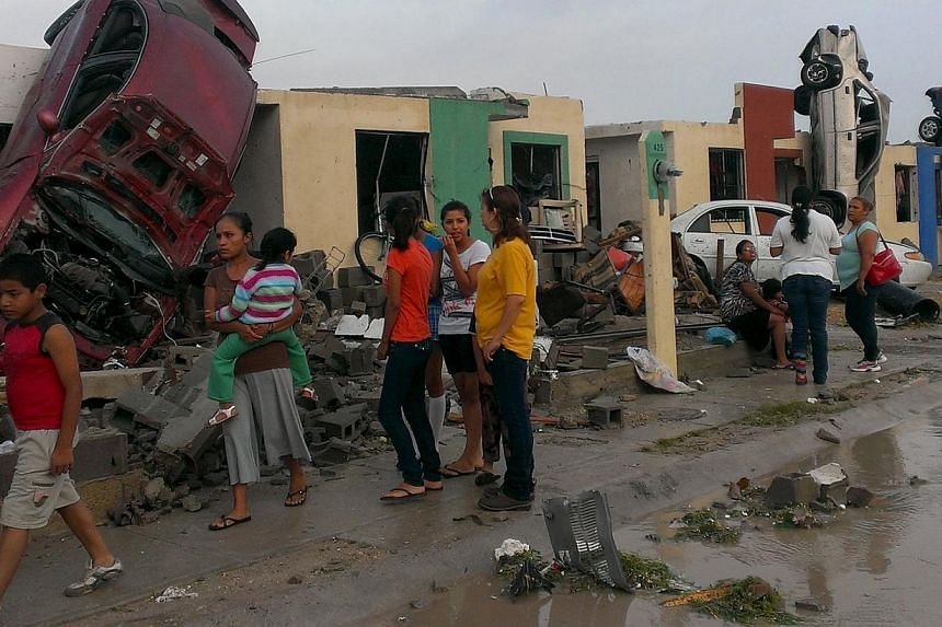 Residents stand outside their homes as damaged cars are seen after a tornado hit the town of Ciudad Acuna, state of Coahuila, May 25, 2015. At least 10 people died on Monday morning after a tornado hit Ciudad Acuna, a Mexican city on the border with