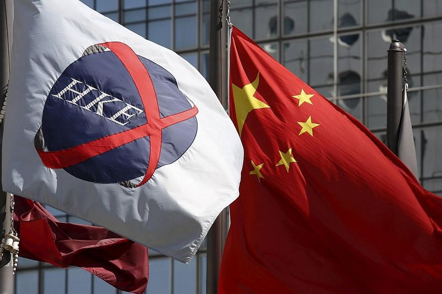 A Chinese national flag (right) flies beside a flag of the Hong Kong Exchanges (HKEx) in Hong Kong on April 15, 2015. Hong Kong's exchange operator headed for a record close and brokerages surged on optimism that policy changes in China will spur inf