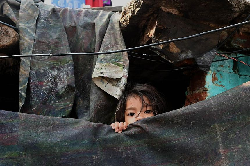 A young girl peeping out from her shanty in a slum in New Delhi on March 18, 2015. -- PHOTO: AFP