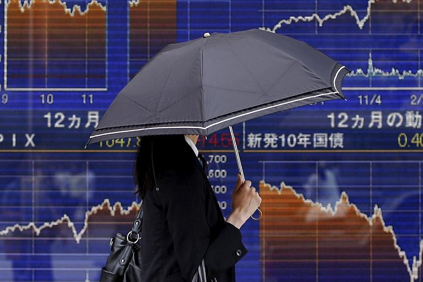 A pedestrian walking past an electronic board showing the graph of the recent fluctuations of Japan's Nikkei average outside a brokerage in Tokyo, Japan, on May 20, 2015. -- PHOTO: REUTERS