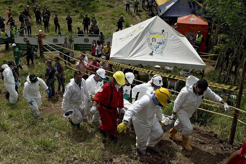 Forensic personnel and rescue workers carry the corpse of one of the fifteen miners who were trapped by the collapse of a gold mine, near the area of El Saibo, in Riosucio, Caldas department, Colombia, on May 15, 2015. -- PHOTO: AFP