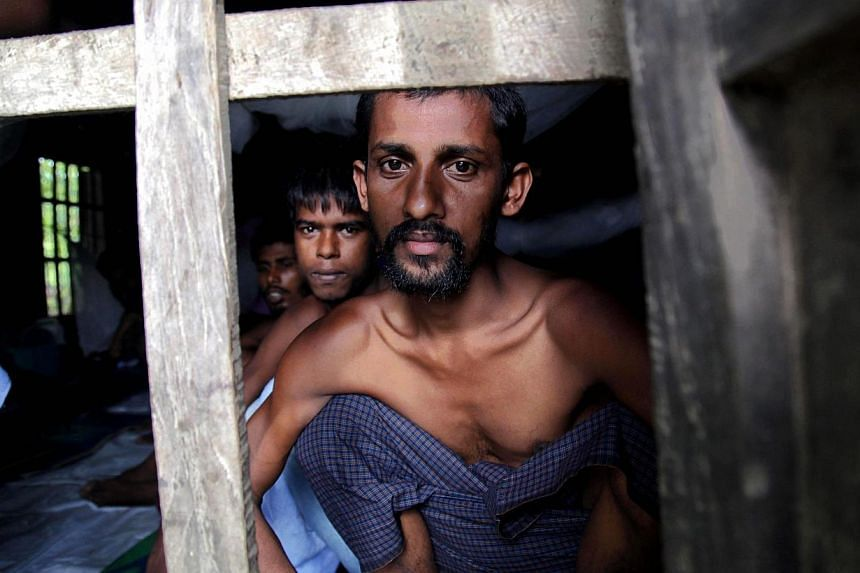 Rohingya Muslims from Bangladesh rescued by the Myanmar navy sit inside buildings at a temorary refugee camp in the village of Aletankyaw in the Maungdaw township of northern Rakhine state, Myanmar, on May 23, 2015. -- PHOTO: EPA