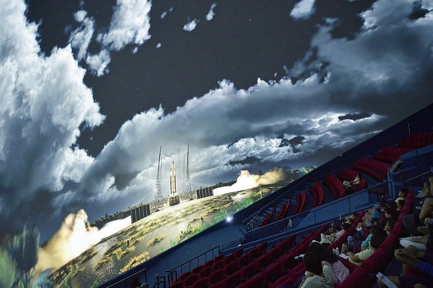 """Guests watch the digital fulldome movie """"Back to the Moon for Good"""" during the media preview of the newly revamped omni-theatre at the Science Centre Singapore on May 25, 2015. -- ST PHOTO: MARK CHEONG"""