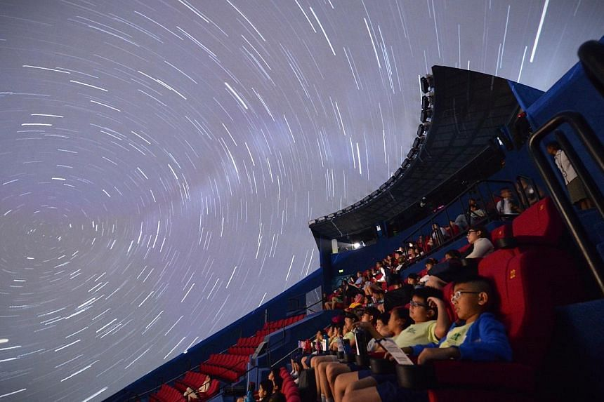 Guests watch the movie accompanying the live show by science educators Yong Jian-Yi and Ishak Khan during the media preview of the newly revamped omni-theatre at the Science Centre Singapore on May 25, 2015. -- ST PHOTO: MARK CHEONG