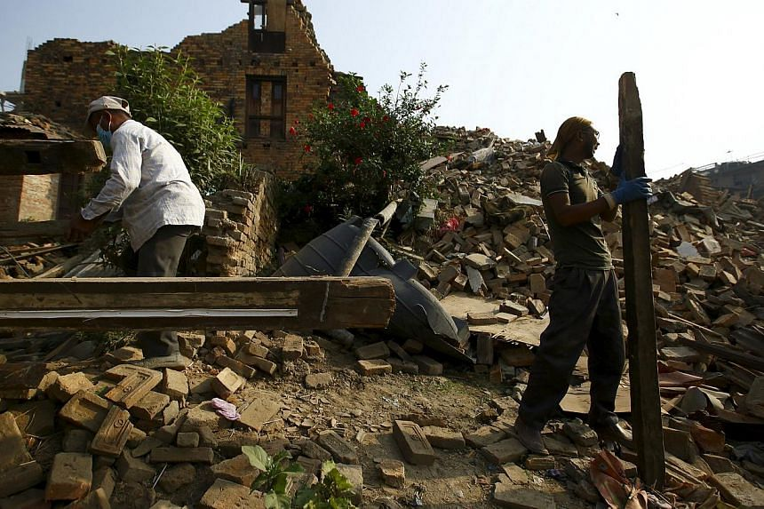 Two men working to clear debris from a collapsed house, a month after the April 25 earthquake in Kathmandu, Nepal on May 25, 2015. -- PHOTO: REUTERS