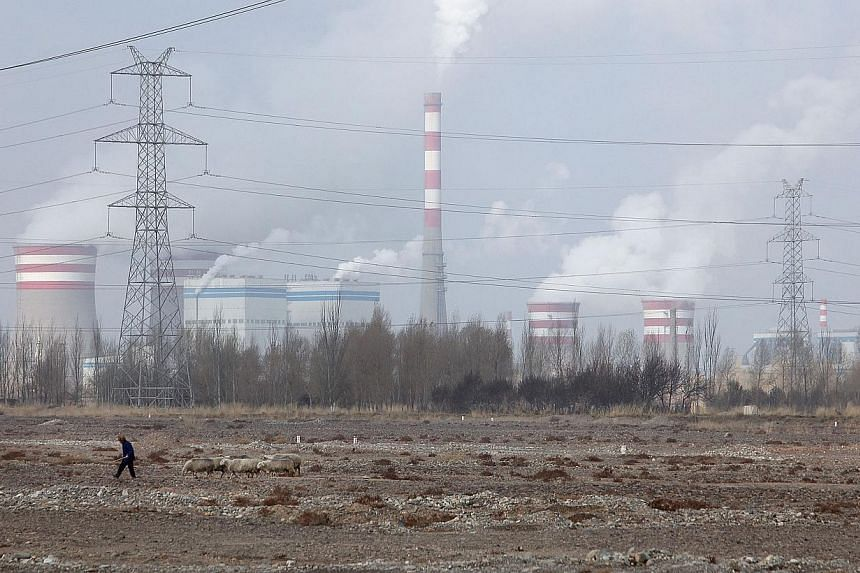Coal-fired power plants like this in Jiuquan, Gansu province, China, could lock in decades of rising carbon dioxide pollution, with CO2 the main greenhouse gas blamed for climate change. Protests in Central Java last month (right), by farmers and fis