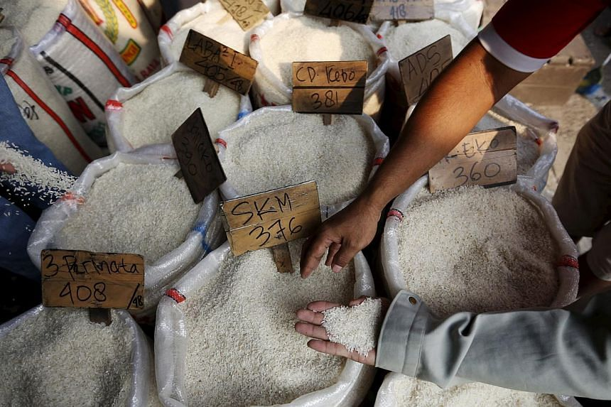 Customers checking the quality of rice at a wholesale rice market in east Jakarta last week. One lab test on rice samples collected from a stall in Bekasi showed traces of PVC. -- PHOTO: REUTERS