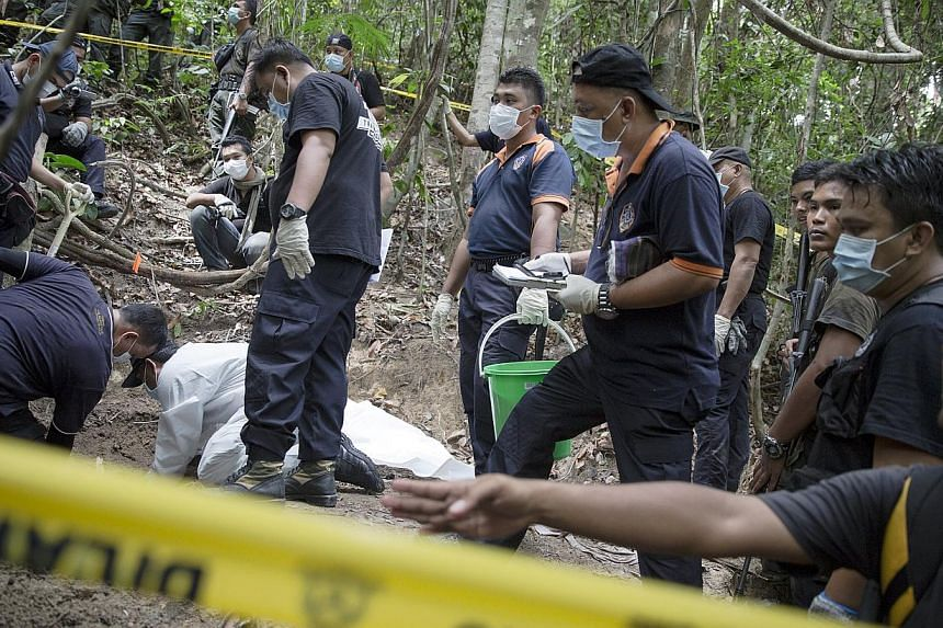 Policemen monitor as forensic experts dig out human remains near the abandoned human trafficking camp in the jungle close the Thailand border at Bukit Wang Burma in northern Malaysia May 26, 2015. -- PHOTO: REUTERS