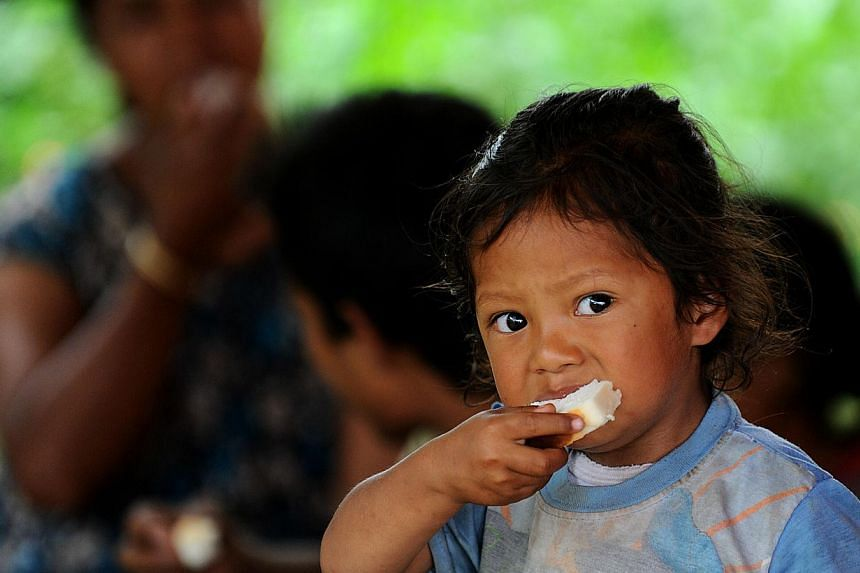 A Nepalese child eats at a relief camp for survivors of the Nepal earthquake in Baktarpur on the outskirts of Kathmandu on May 20, 2015. Nepal on Tuesday, May 26, banned children from travelling without parents or approved guardians in a bid to deter