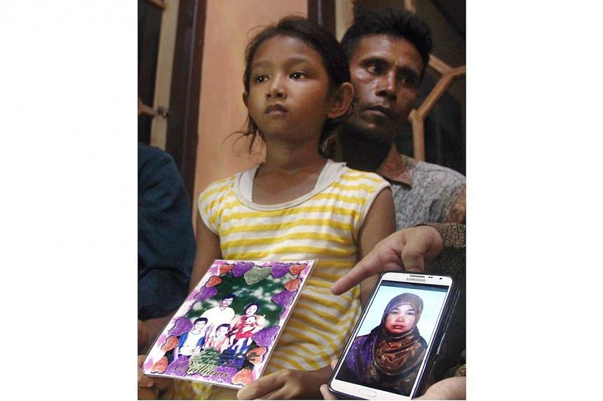 In this file photograph taken on April 17, 2015, Desi Sri Rahayu, the ten-year-old daughter of Karni binti Medi Tarsim, an Indonesian domestic worker executed in Saudi Arabia, holds her mother's family potrait as she sits with her father Darpin at th