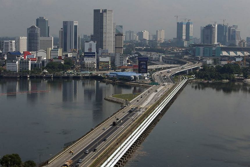 The Immigration & Checkpoints Authority (ICA) issued an advisory to warn travellers to expect delays at the Woodlands and Tuas checkpoints. -- PHOTO: REUTERS
