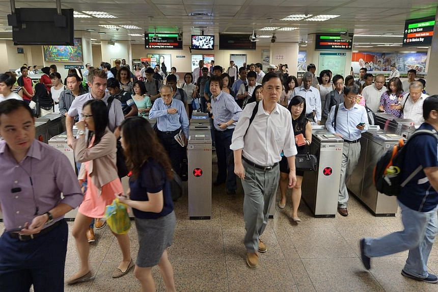 Commuters at Raffles Place MRT station. The Land Transport Authority is extending free pre-peak travel on the rail network for another year, to June 30, 2016. -- PHOTO: ST FILE