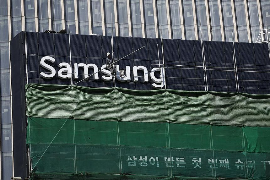 A worker works on a Samsung outdoor advertisement installed atop an office building in central Seoul on March 23, 2015. Samsung Group announced Tuesday the merger of two major affiliates as the South Korean business giant accelerates restructuring ef