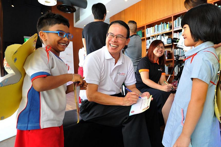 Mayor for North West CDC Dr Teo Ho Pin (centre) writing Go Green Pledge Cards with children from PCF Sparkletots Woodlands during a media preview of CDCs Celebrating Communities, a community parade and brisk walk to be held at Marina Bay this coming