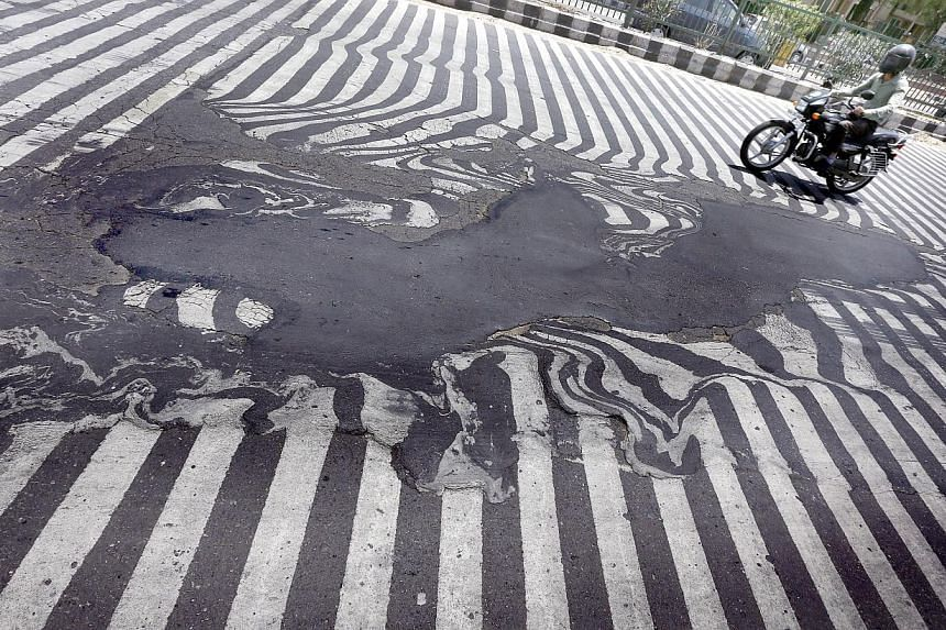 A motorcyclist rides past road markings that appear distorted due to the road asphalt melting and beginning to run, in New Delhi on May 27, 2015. Indian authorities have cancelled doctors' leave to help cope with the sick, as a heat wave spread acros