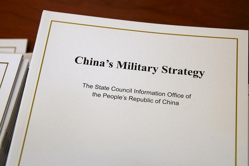 Copies of the annual white paper on China's military strategy are placed on a table for distribution to journalists during a news conference in Beijing, China, May 26, 2015. China outlined a defence strategy on Tuesday to boost its naval capability f