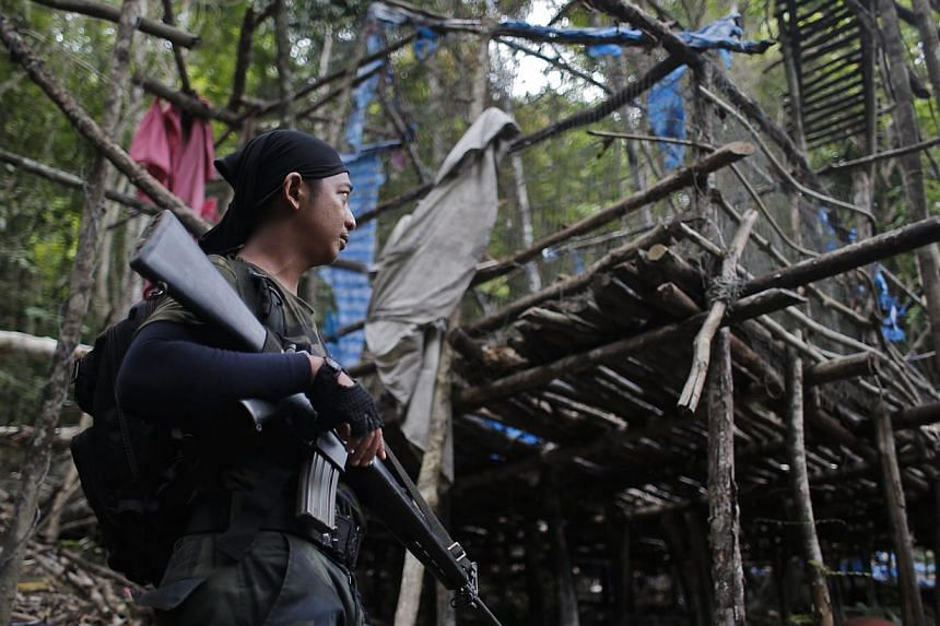 An armed officer from the Royal Malaysia Police standing guard at an abandoned camp at Wang Burma hills in Wang Kelian, Perlis, on May 26, 2015. -- PHOTO: EPA