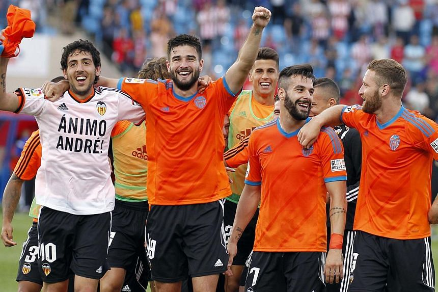 Valencia's players celebrate their qualification for the Champions League after the Spanish league football match between UD Almeria and Valencia CF at the Juegos Mediterraneos stadium in Almeria on May 23, 2015. The Spanish football club announced o