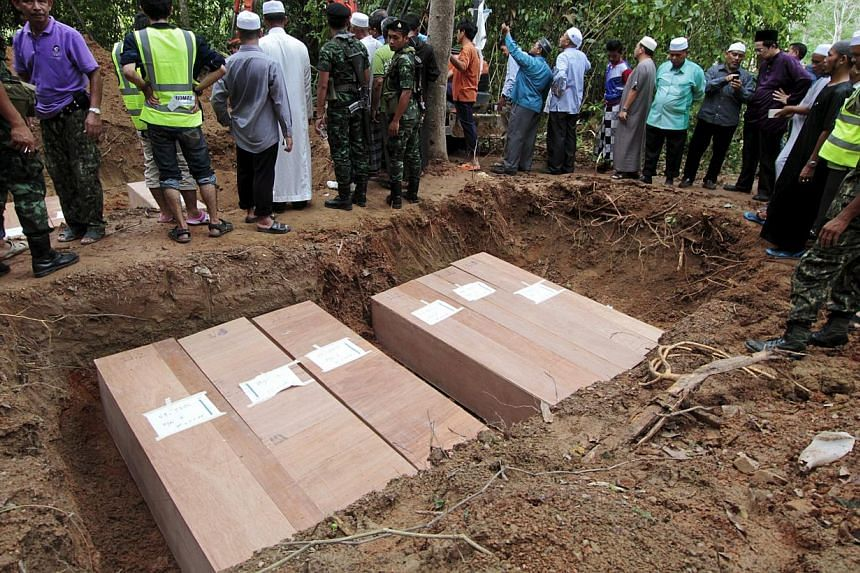 Thai Muslim villagers and security forces watch as coffins containing the remains of Rohingya migrants are placed in a grave for burial after a funeral at a graveyard in Thailand's southern Songkhla province on May 10, 2015. -- PHOTO: REUTERS