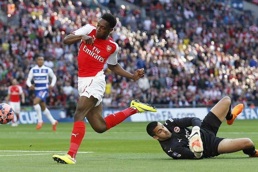 Arsenal's Danny Welbeck (left) pushes the ball past Reading keeper Adam Federici during the FA Cup Semi Final at Wembley Stadium on April 18, 2015. Arsenal manager Arsene Wenger has said that Welbeck will miss the team's FA Cup Final clash against As