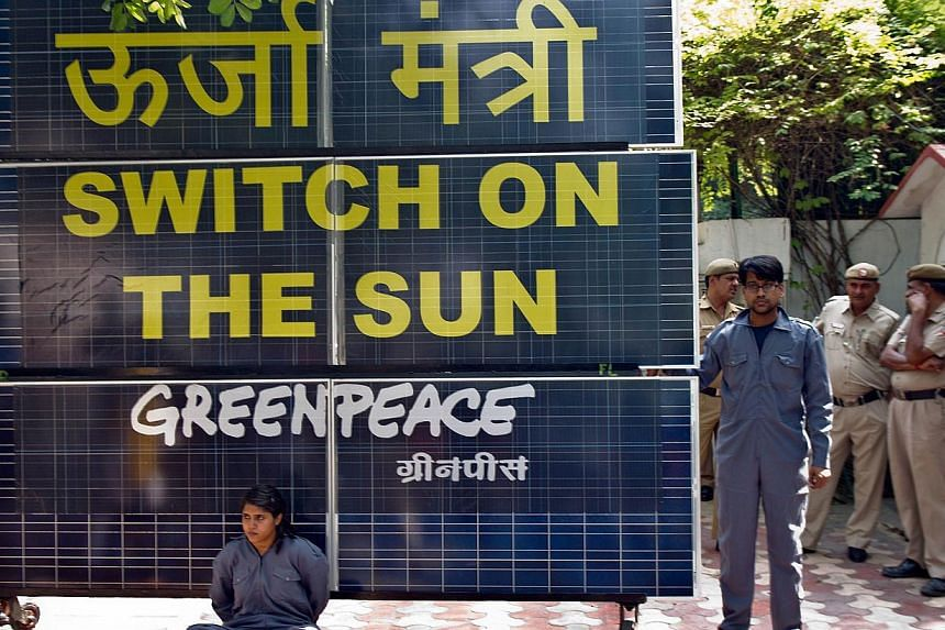 Greenpeace activists chained to a bank of solar panels blocking the entry to the residence of Delhi's then Power Minister Haroon Yusuf in New Delhi, on May 15, 2013. A court in New Delhi on Wednesday, May 27, 2015, ordered authorities to unfreeze Gre