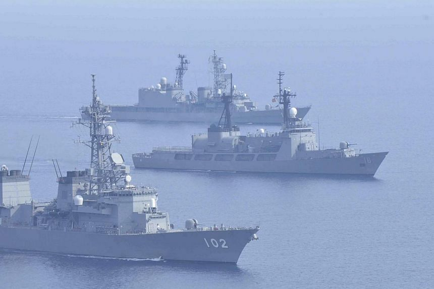 Japanese Maritime Self-Defence Force destroyers Harusame (bottom) and Amagiri (top) sail side by side with Philippine warship BRP Ramon Alcaraz during a joint naval drill in the South China Sea on May 12, 2015. The two nations are set to bolster secu