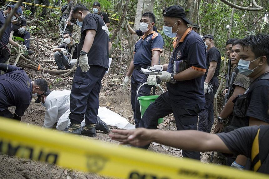 Policemen monitor as forensic experts dig out human remains near the abandoned human trafficking camp in the jungle close to the Thailand border at Bukit Wang Burma in northern Malaysia on May 26, 2015. -- PHOTO: REUTERS