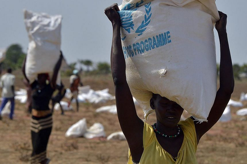 A woman carries a sack of food aid after a food-drop in a field on February 23, 2015 at a village in Nyal, Panyijar county, near the northern border with Sudan.-- PHOTO: AFP