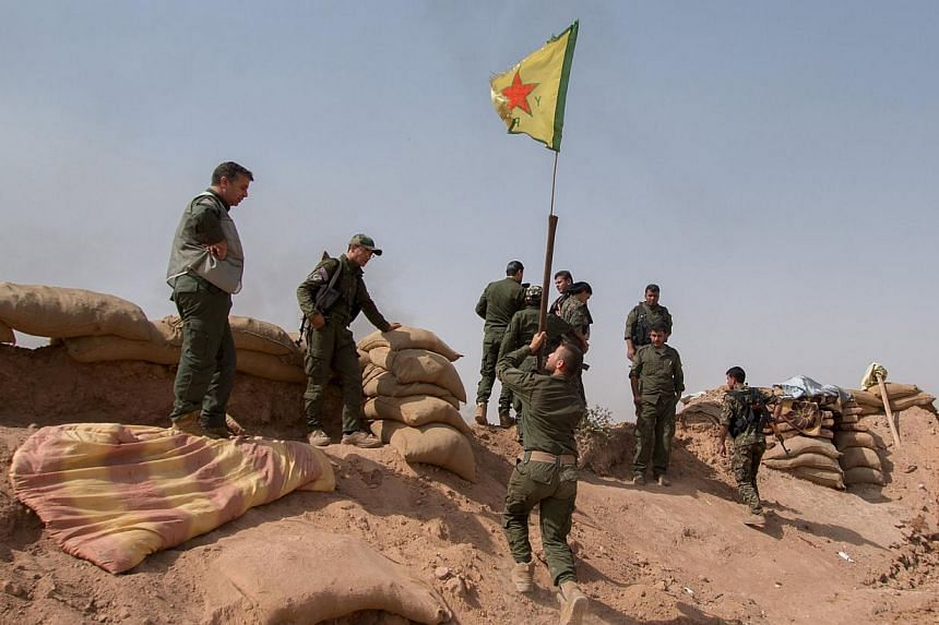 Kurdish People's Protection Unit (YPG) fighters raise a YPG flag over a barrier in Tel al-Aghbish village, which they said they retook control of from the Islamic State in Iraq and Syria (ISIS) on May 21, 2015. A group monitoring the war on Wednesday