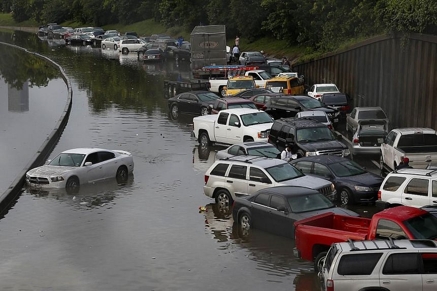 Vehicles left stranded on a flooded Interstate 45 in Houston on Tuesday. Heavy rains and flooding put the city of Houston under massive ammounts of water, closing roadways and trapping residents in their cars and buildings, -- PHOTO: AFP